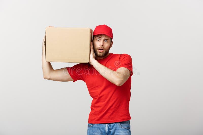 Concepto de la entrega - el retrato del hombre de entrega hermoso caucásico curioso escucha dentro de un paquete de la caja Aisla fotografía de archivo