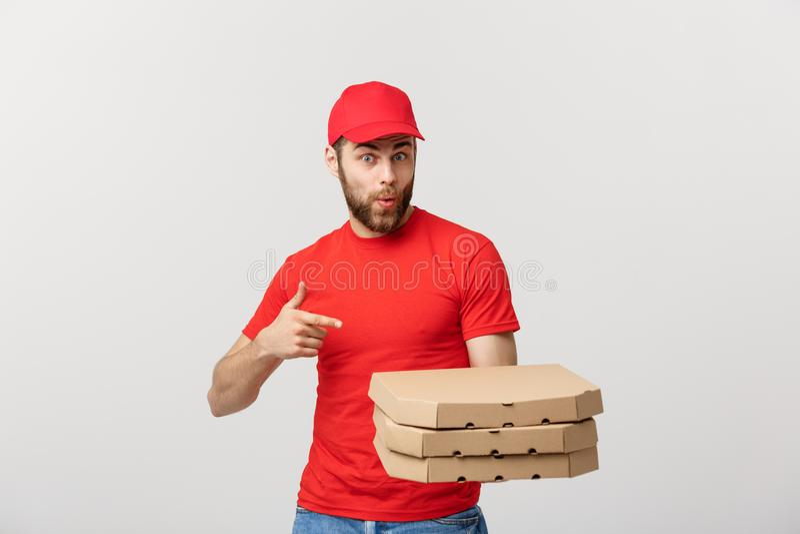 Concepto de la entrega: Hombre de entrega caucásico hermoso de la pizza que señala el finger Aislado sobre fondo gris fotos de archivo