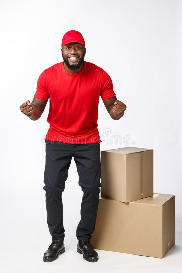 Concepto de la entrega - retrato del hombre de entrega afroamericano feliz en el paño rojo que lleva a cabo un paquete de la caja fotos de archivo