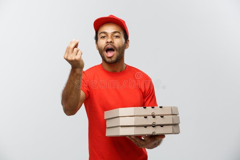 Concepto de la entrega - retrato del hombre de entrega afroamericano feliz que muestra gesto delicioso a mano con sostener las ca foto de archivo