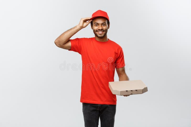 Concepto de la entrega - retrato del hombre de entrega afroamericano hermoso de la pizza Aislado en fondo gris del estudio copia imagen de archivo