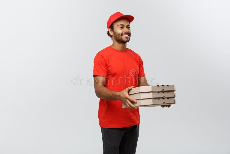 Concepto de la entrega - retrato del hombre de entrega afroamericano hermoso de la pizza Aislado en fondo gris del estudio copia fotos de archivo