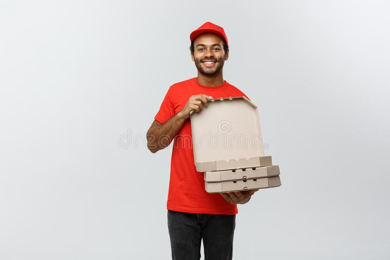 Concepto de la entrega - retrato del hombre de entrega afroamericano hermoso de la pizza Aislado en fondo gris del estudio copia foto de archivo