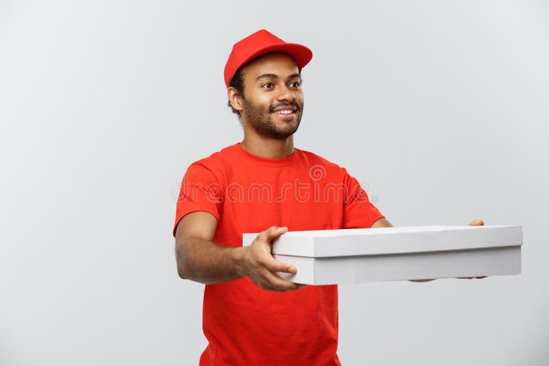 Concepto de la entrega - retrato del hombre de entrega afroamericano hermoso de la pizza Aislado en fondo gris del estudio copia fotos de archivo libres de regalías