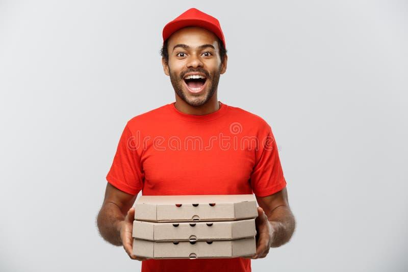 Concepto de la entrega - retrato del hombre de entrega afroamericano hermoso de la pizza Aislado en fondo gris del estudio copia fotografía de archivo