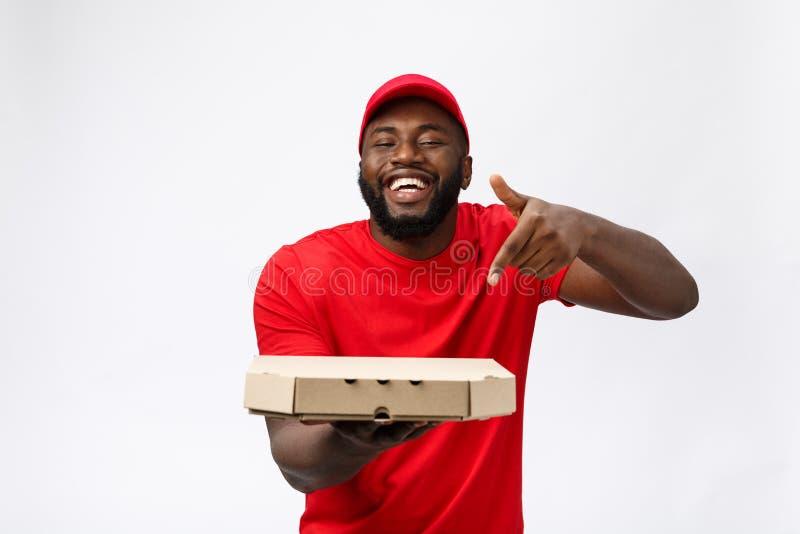 Concepto de la entrega - retrato del hombre de entrega afroamericano hermoso de la pizza Aislado en fondo gris del estudio copia imagenes de archivo
