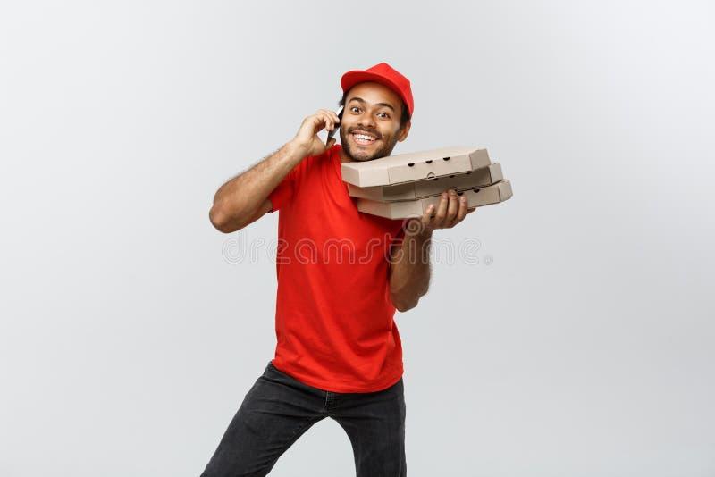 Concepto de la entrega - retrato del hombre de entrega afroamericano hermoso de la pizza en el teléfono con el cliente Aislado en foto de archivo libre de regalías