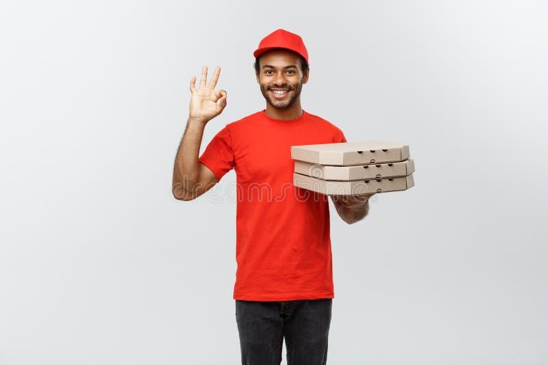 Concepto de la entrega - retrato del hombre de entrega afroamericano hermoso de la pizza que hace la muestra aceptable con los fi fotos de archivo