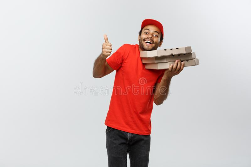 Concepto de la entrega - retrato del hombre de entrega afroamericano hermoso de la pizza que muestra golpe para arriba Aislado en fotos de archivo libres de regalías