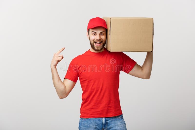 Concepto de la entrega - retrato del hombre de entrega caucásico feliz que señala la mano para presentar un paquete de la caja Ai imagen de archivo libre de regalías
