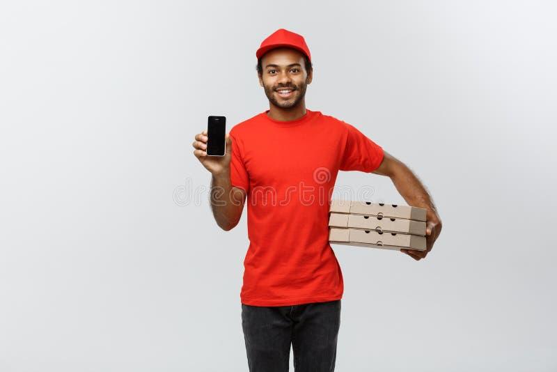 Concepto de la entrega - retrato del hombre o del mensajero afroamericano hermoso de entrega con la caja de la pizza que muestra  imagen de archivo libre de regalías