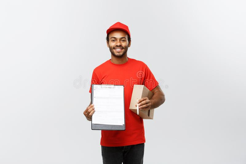 Concepto de la entrega - retrato del hombre o del mensajero afroamericano hermoso de entrega que muestra una forma del documento  imágenes de archivo libres de regalías