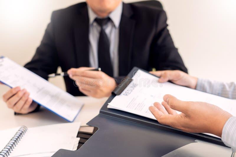 Concepto de la entrevista y del alquiler de trabajo, hombre de negocios del candidato de la cita que explica sobre su perfil y re imagen de archivo