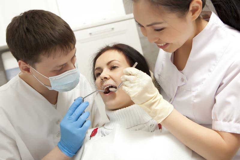 Concepto de la estomatología - dentista con el espejo que comprueba a la muchacha paciente imagen de archivo libre de regalías