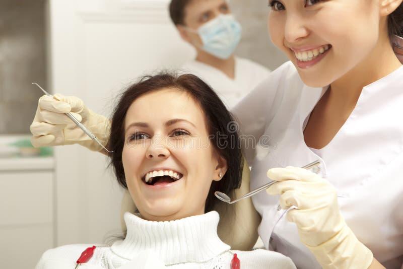 Concepto de la estomatología - dentista con el espejo que comprueba a la muchacha paciente imágenes de archivo libres de regalías