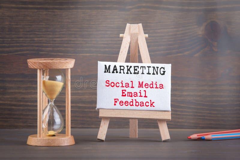 Concepto de la estrategia de marketing Contador de tiempo de Sandglass, del reloj de arena o del huevo en la tabla de madera imagen de archivo