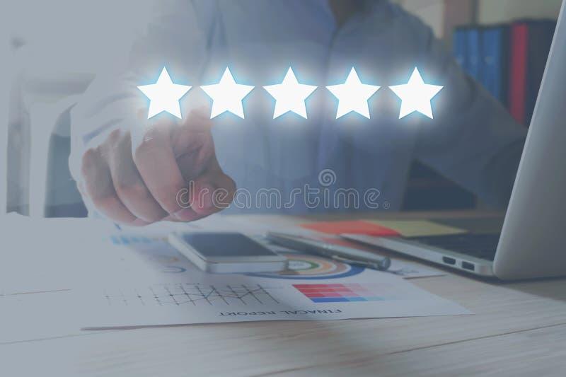 Concepto de la evaluación Hombre de negocios que señala la estrella cinco al grado del aumento de la compañía fotos de archivo libres de regalías