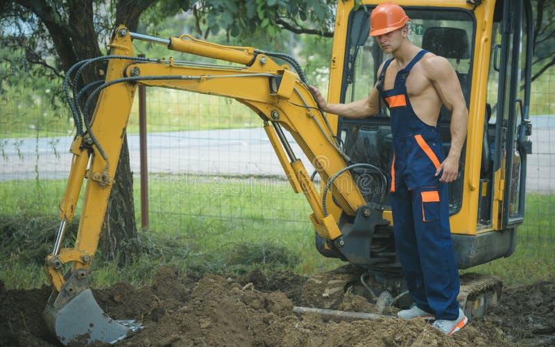 Concepto de la excavación Excavador actuado hombre para la excavación de tierra Trabajo picador del operador sobre sitio de la ex imagen de archivo libre de regalías