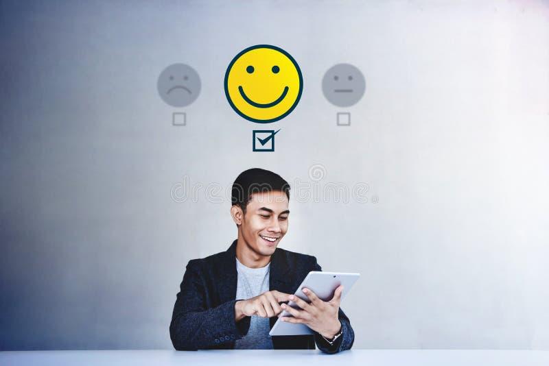 Concepto de la experiencia del cliente Hombre de negocios joven Giving su estudio positivo en encuesta sobre en l?nea la satisfac foto de archivo