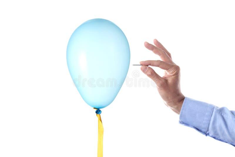 Concepto de la explosión de las finanzas: la mano caucásica del ` s del hombre que sostenía un clavo estalló un globo del partido imágenes de archivo libres de regalías