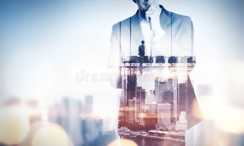 Concepto de la exposición doble con el hombre de negocios y la ciudad de pensamiento con fotos de archivo libres de regalías