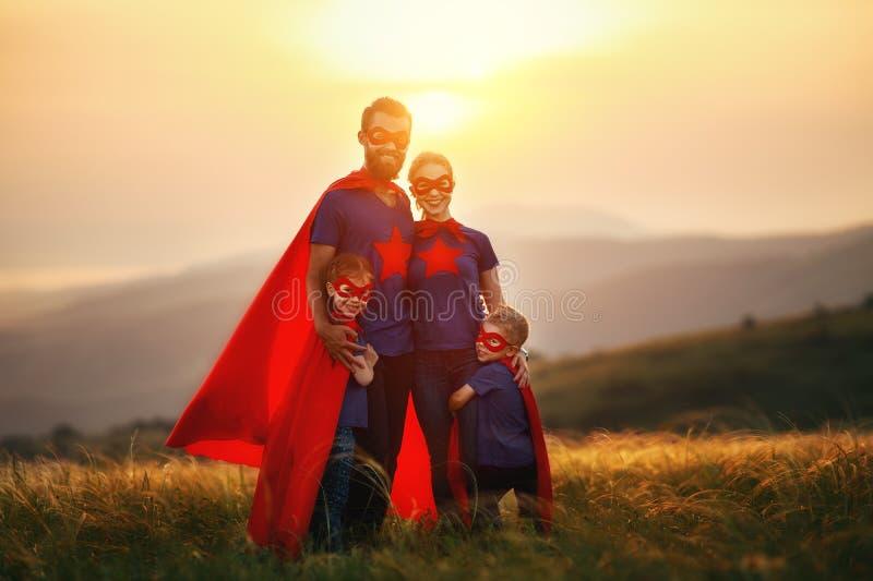 Concepto de la familia estupenda, familia de super héroes en la puesta del sol fotografía de archivo