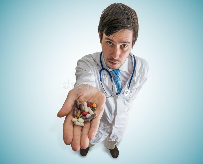 Concepto de la farmacia y de la farmacología El doctor sostiene muchas píldoras disponibles foto de archivo libre de regalías