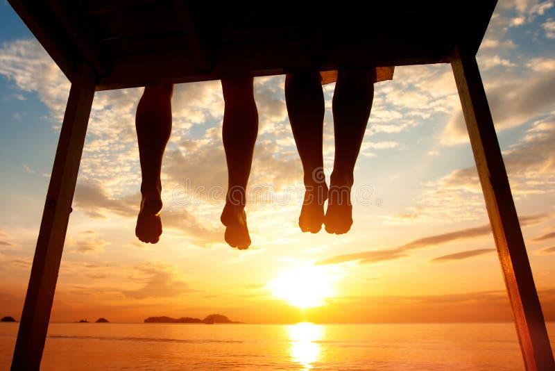 Concepto de la felicidad, silueta de pies de pares que se sientan en el embarcadero en la playa foto de archivo