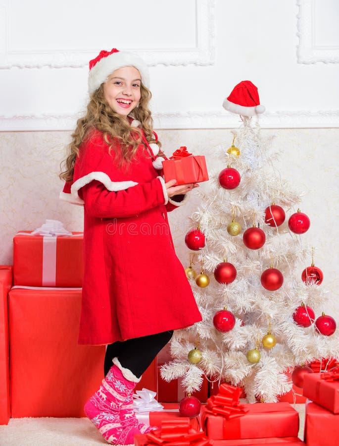 Concepto de la Feliz Año Nuevo Desempaque del regalo de la Navidad Tradición de las vacaciones de invierno La muchacha celebra la imagenes de archivo