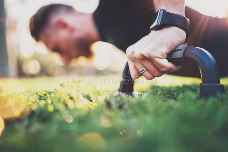 Concepto de la forma de vida de Crossfit Opinión del primer de la mano masculina mientras que hace flexiones de brazos en el parq imagen de archivo