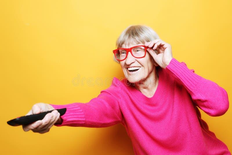 Concepto de la forma de vida, del tehnology y de la gente: la abuela divertida está sosteniendo un telecontrol de la TV sobre fon imágenes de archivo libres de regalías