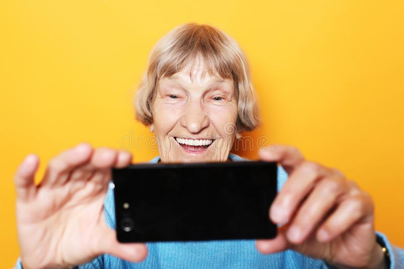 Concepto de la forma de vida, del tehnology y de la gente: la abuela en suéter azul sonríe y toma un selfie imagenes de archivo