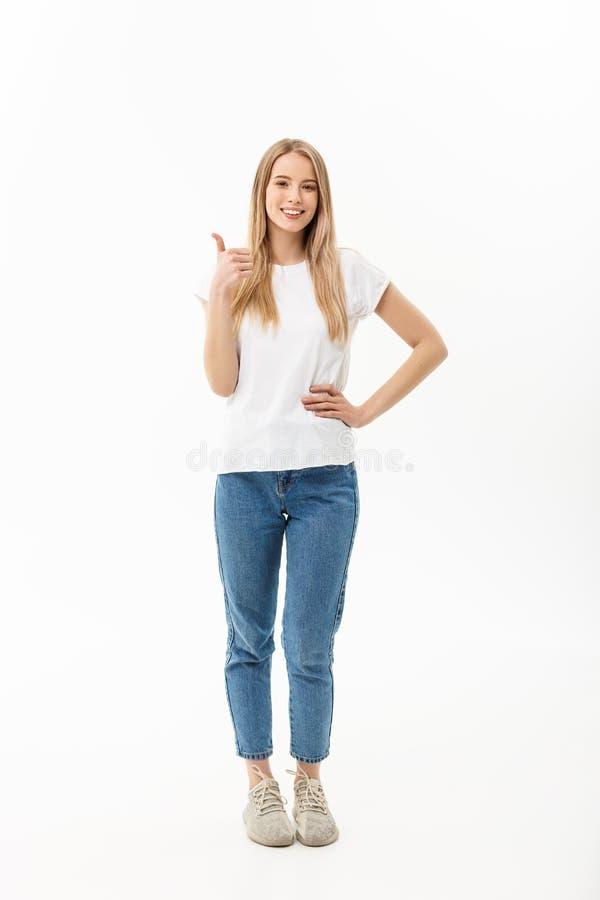 Concepto de la forma de vida: Mujer joven sonriente feliz en vaqueros mirando el donante de la cámara pulgares para arriba del éx fotografía de archivo