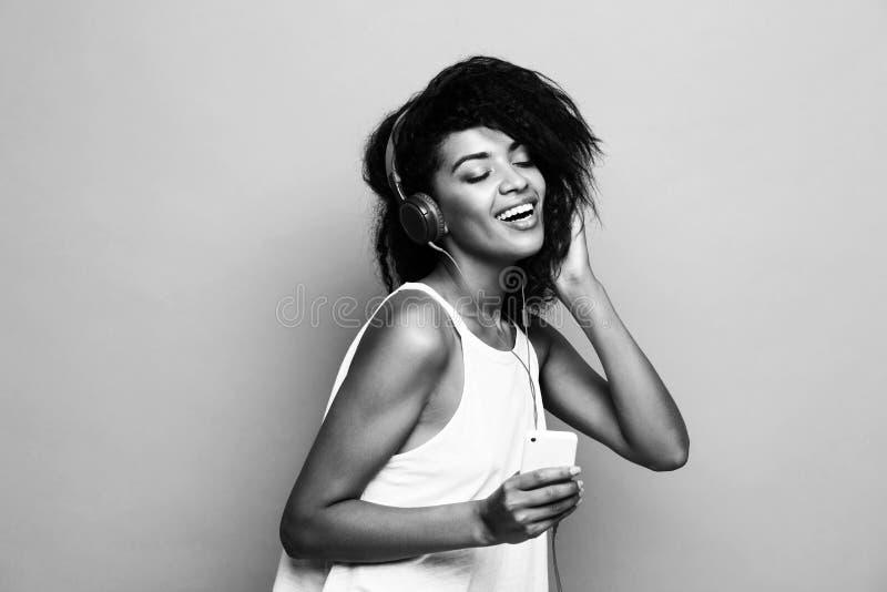 Concepto de la forma de vida - retrato de escuchar alegre de la mujer afroamericana hermosa la música en el teléfono móvil amaril fotografía de archivo