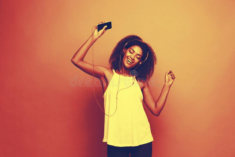 Concepto de la forma de vida - retrato de escuchar alegre de la mujer afroamericana hermosa la música en el teléfono móvil Copie  fotos de archivo libres de regalías