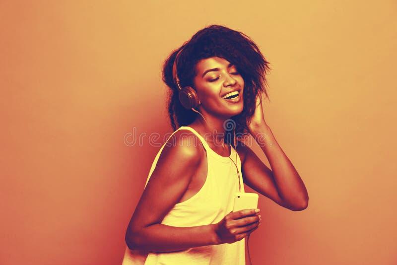 Concepto de la forma de vida - retrato de escuchar alegre de la mujer afroamericana hermosa la música en el teléfono móvil pastel imagen de archivo libre de regalías