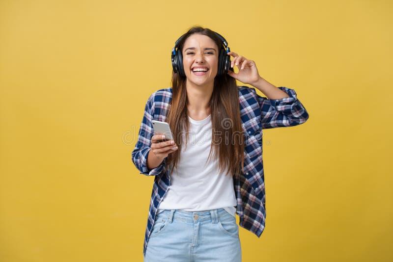 Concepto de la forma de vida - retrato de escuchar alegre de la mujer caucásica hermosa la música en el teléfono móvil Pastel ama imágenes de archivo libres de regalías