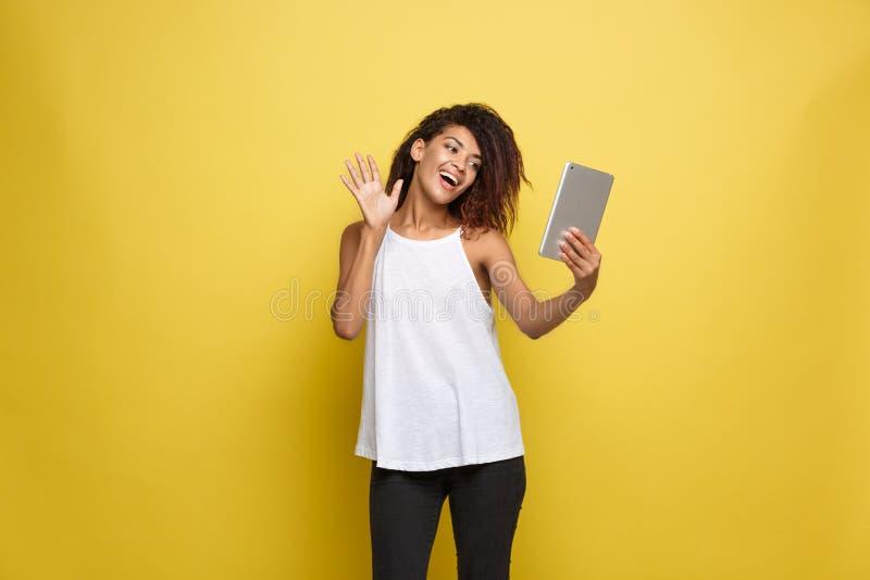Concepto de la forma de vida - retrato de la mujer afroamericana hermosa alegre jugando algo en la tableta electrónica amarillo imágenes de archivo libres de regalías