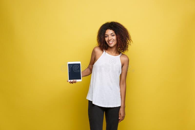 Concepto de la forma de vida - retrato de la mujer afroamericana hermosa alegre presentando algo en la tableta electrónica imagen de archivo libre de regalías