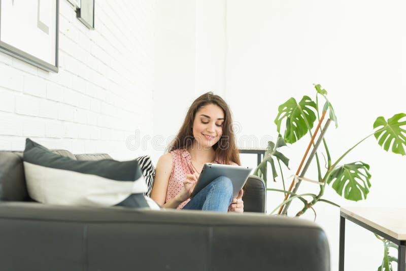 Concepto de la gente, del interior y del ocio - mujer joven feliz con la PC de la tableta que pone en el sofá foto de archivo