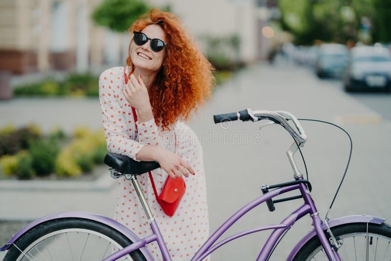 Concepto de la gente, del ocio, de la forma de vida y del tiempo libre La mujer rizada alegre enfocada en distancia, monta la bic foto de archivo libre de regalías