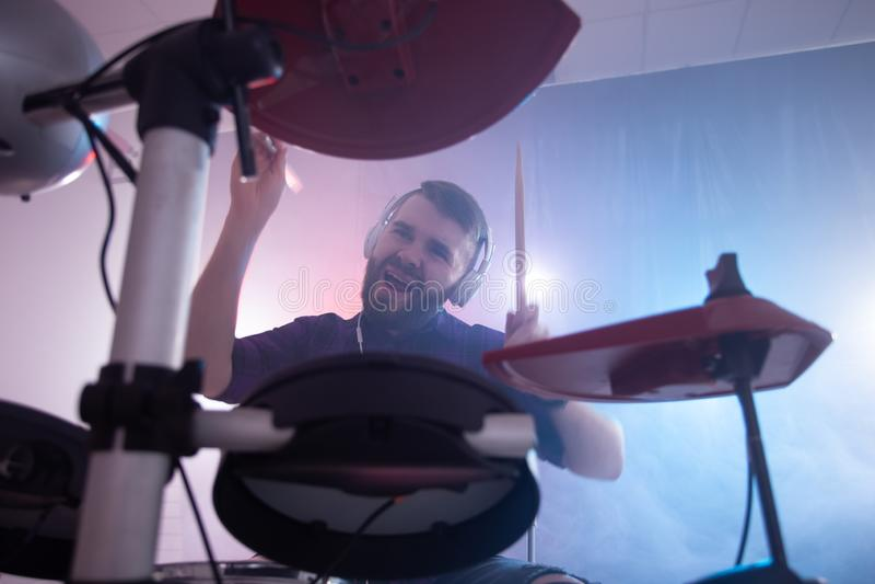 Concepto de la gente, de la música y de la afición - hombre que juega los tambores sobre la iluminación del fondo en la etapa foto de archivo libre de regalías