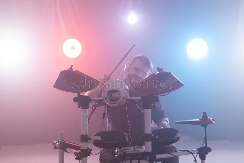 Concepto de la gente, de la música y de la afición - juegos del hombre con los palillos en los tambores en la etapa fotos de archivo