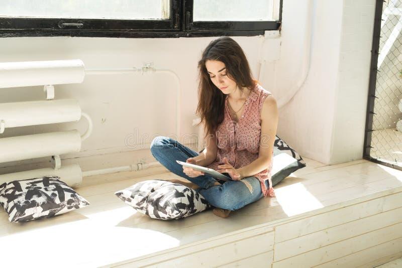 Concepto de la gente, de la tecnología y de Internet - mujer joven que usa la tableta digital en casa fotos de archivo