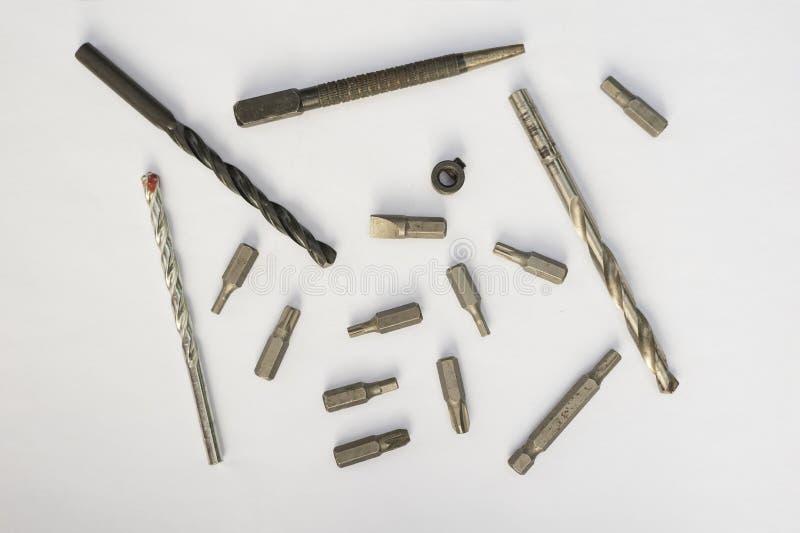 Concepto de la herramienta del trabajo Fije de taladros y de pedazos para un destornillador en un fondo blanco Directamente arrib imagenes de archivo