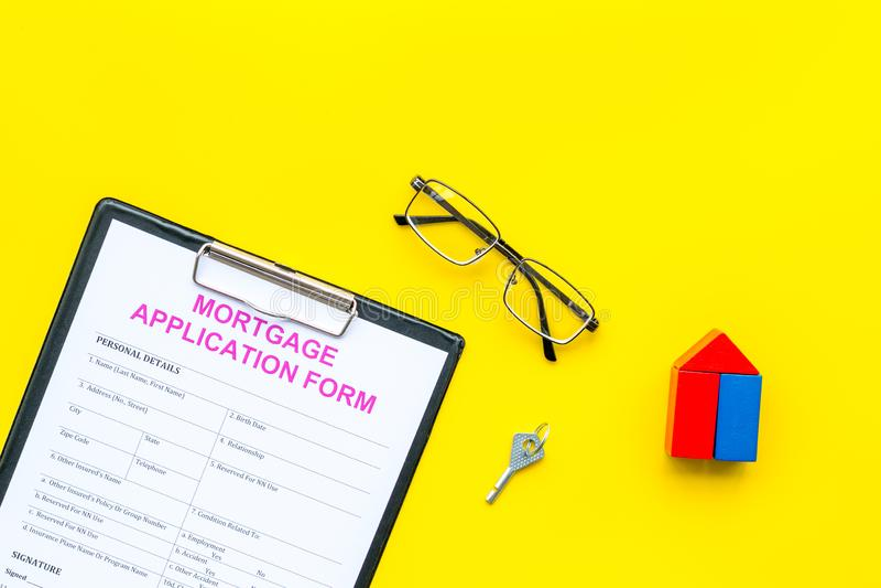 Concepto de la hipoteca La forma de la solicitud de hipoteca cerca de la llave y de la casa hizo de constructor en copia amarilla fotos de archivo libres de regalías