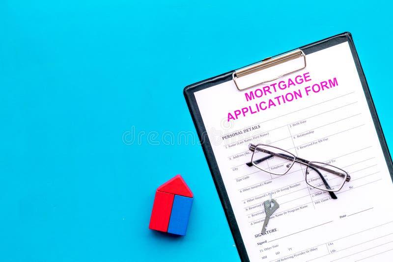 Concepto de la hipoteca La forma de la solicitud de hipoteca cerca de la llave y de la casa hizo de constructor en el espacio azu fotos de archivo