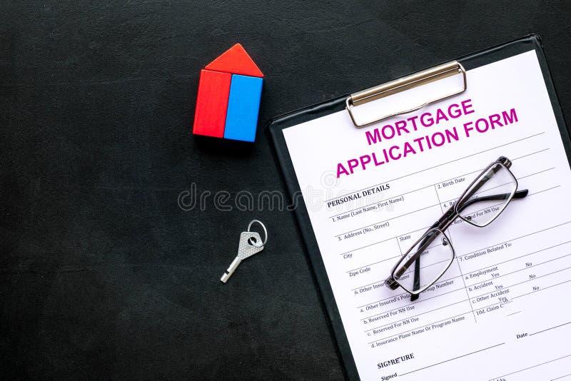 Concepto de la hipoteca La forma de la solicitud de hipoteca cerca de la llave y de la casa hizo de constructor en espacio negro  imagenes de archivo
