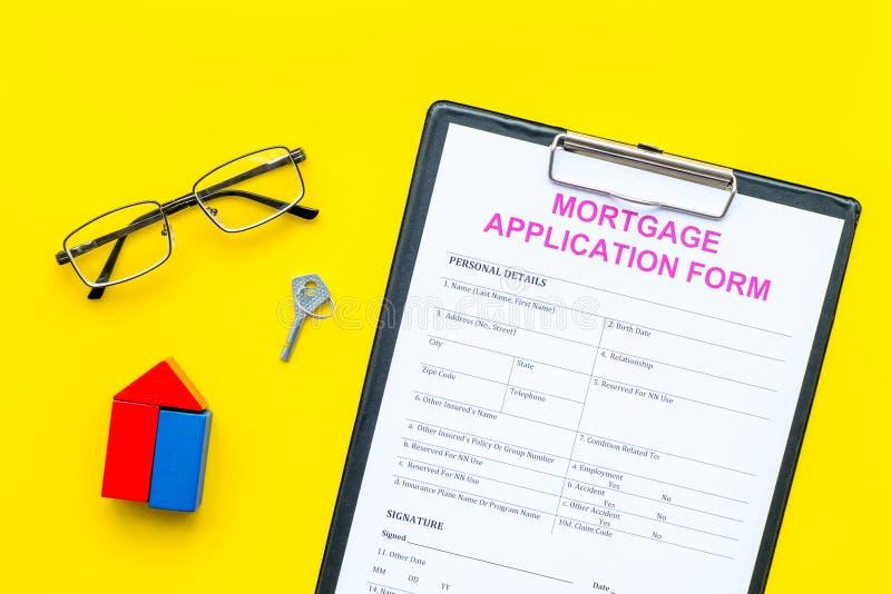 Concepto de la hipoteca La forma de la solicitud de hipoteca cerca de la llave y de la casa hizo de constructor en la opinión sup imagen de archivo