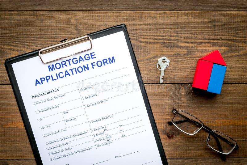 Concepto de la hipoteca La forma de la solicitud de hipoteca cerca de la llave y de la casa hizo de constructor en la opinión de  imagen de archivo libre de regalías